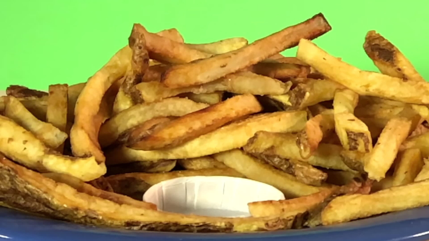 HD slow motion Video of pile of french fries with small white container on a blue plate with green background, wood table, ketchup pouring slow motion into the container. | Shutterstock HD Video #1040721653