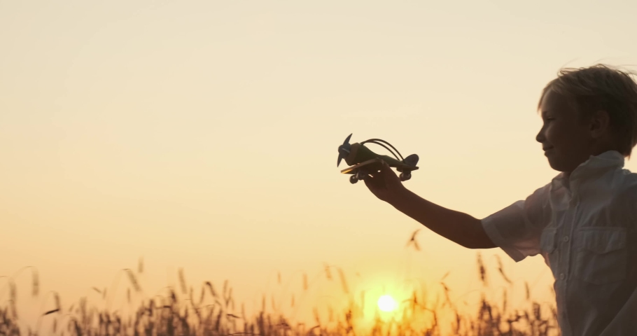 Boy is running with a plane in his hands. Boy is playing with a wooden airplane and dreams of being a pilot. Happy child playing in nature during summer sunset. Happiness of children. Slow motion. #1040725343