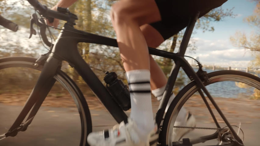 Cycling Athlete At Sunset Fall On City.Gear System Road Bicycle And Bike Wheel Rotation.Close-Up Cyclist Pedaling On City Park At Autumn.Cyclist Twists Pedals And Riding On Road Bicycle.Sport Concept | Shutterstock HD Video #1040729783