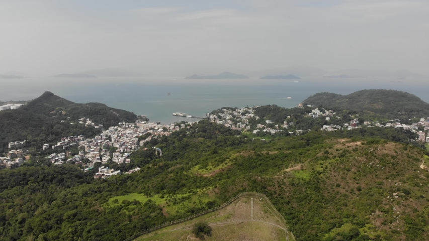 Aerial view the tourist village of Yung Shue Wan, Lamma Island. In the background the sea and other islands. Hong Kong, China   Shutterstock HD Video #1040818943