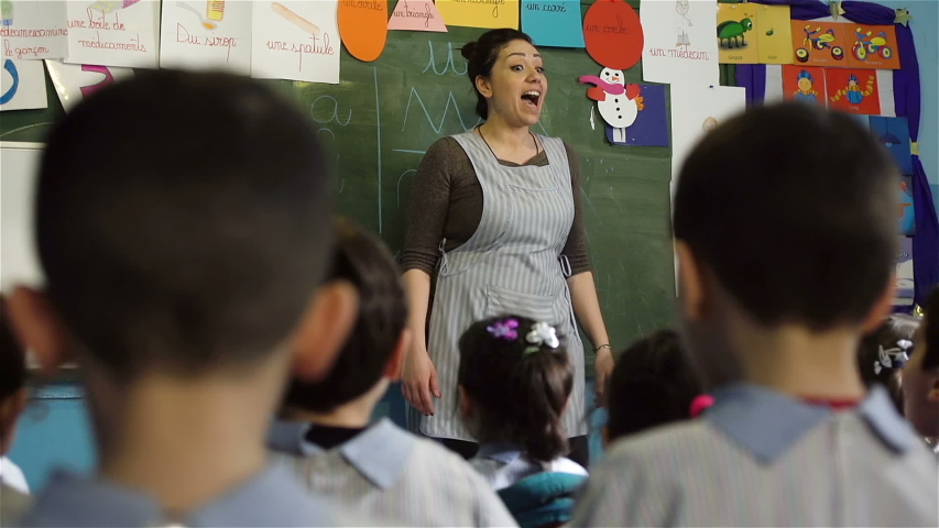 BEIRUT, LEBANON - 2016: Female kindregarten teacher interacts with children. Women make up 22.6% (2011) of the total labour force in Lebanon | Shutterstock HD Video #1040822513