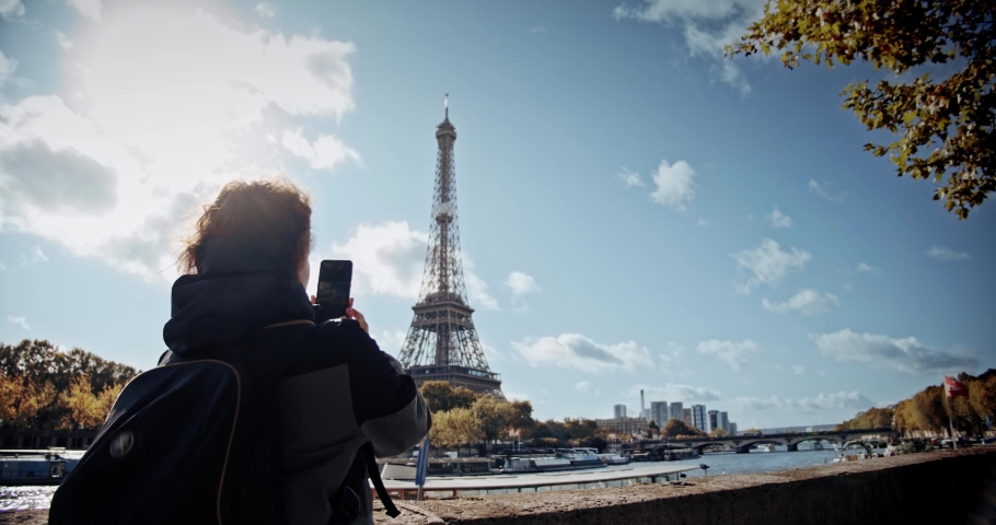 Tourist Girl with backpack looking at Eiffel tower and river Seine and taking photo on smartphone. Wide shot | Shutterstock HD Video #1040971823