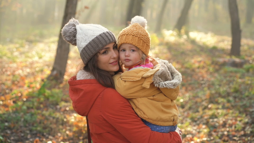 Slow motion video . Little girl kissing on the cheek her mother. Autumn park | Shutterstock HD Video #1040989883