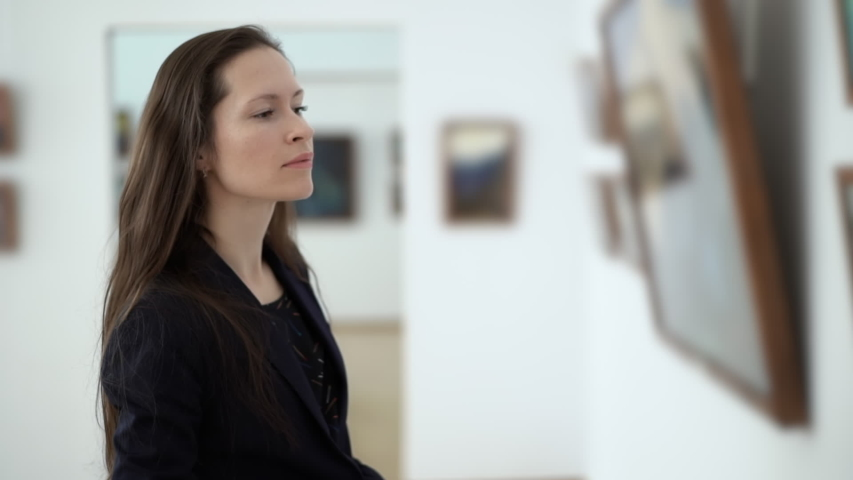 Elegant Beautiful Woman Looks at the Paintings in Gallery During Art Opening Reception. Pictures in the Museum of Modern Art   Shutterstock HD Video #1041058703
