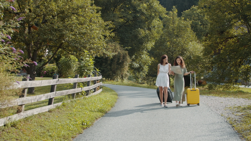 Tourists girlfriends with suitcases using paper map | Shutterstock HD Video #1041082603