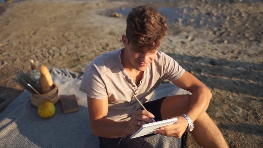 Young artist draws. A man paints a picture sitting on the beach. A handsome man draws.   | Shutterstock HD Video #1041192463