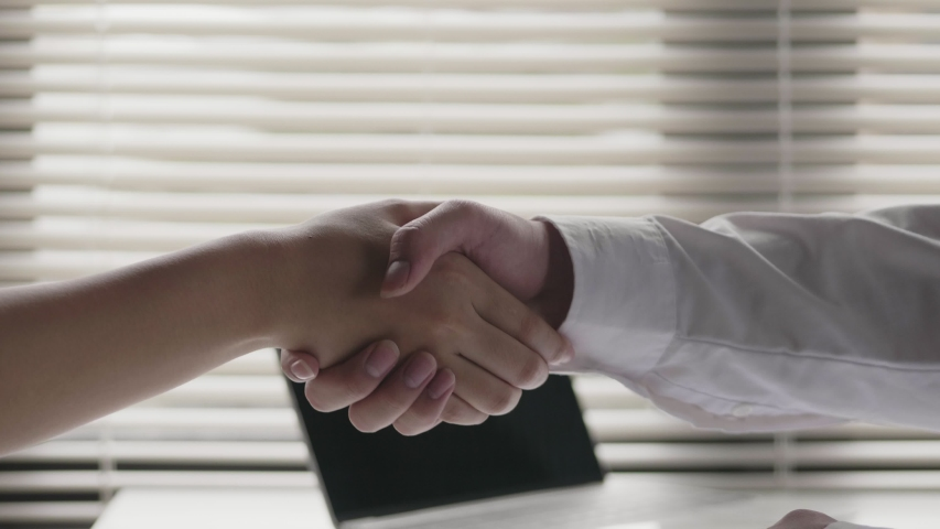 Close up of the Asian businessman shaking hands with businesswoman partners while sitting at the office. | Shutterstock HD Video #1041260863