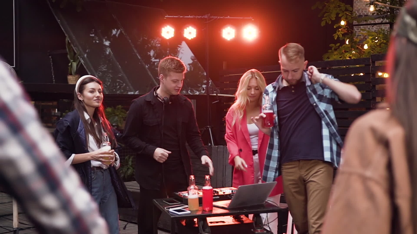 Party, DJ mixing music with mixing console while group of happy young people are dancing and drinking low alcohol drink having fun on celebration. Outdoors. Slow motion | Shutterstock HD Video #1041288073