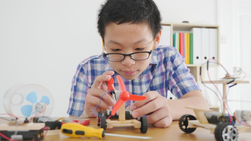 Young Asian boy creating a toy car that is powered by wind from propellers.   | Shutterstock HD Video #1041312133