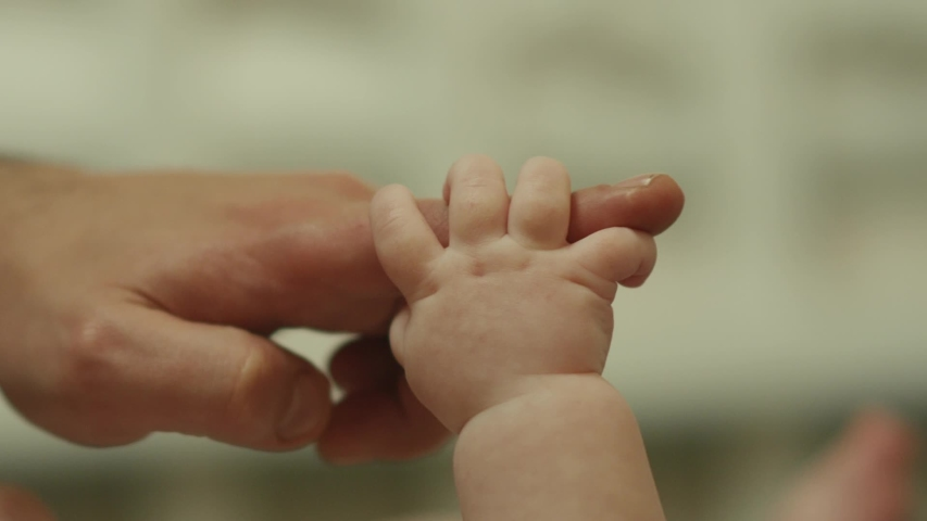 Close-up shot of baby's little cute hand reaching for father's loving finger . Baby holding parent's finger . Parent holding newborns hand in Slow Motion . Hand in hand. Father and his newborn baby .  | Shutterstock HD Video #1041345943