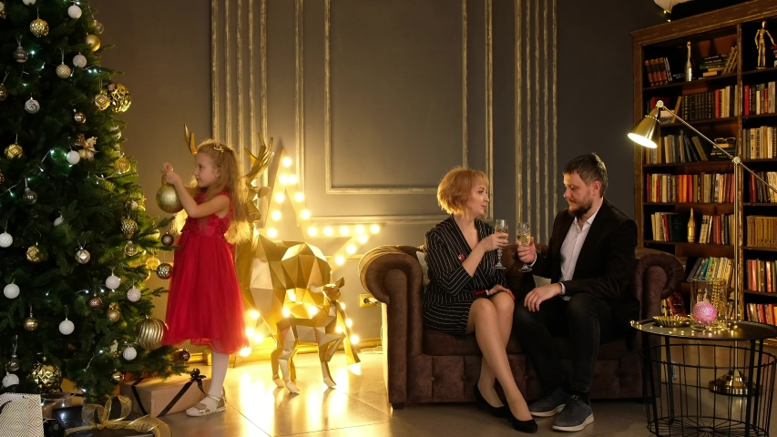 Beautiful man and woman sitting on the couch and drinking sparkling wine, and a little girl decorating the christmas tree. The family celebrates the new year at home. | Shutterstock HD Video #1041456673