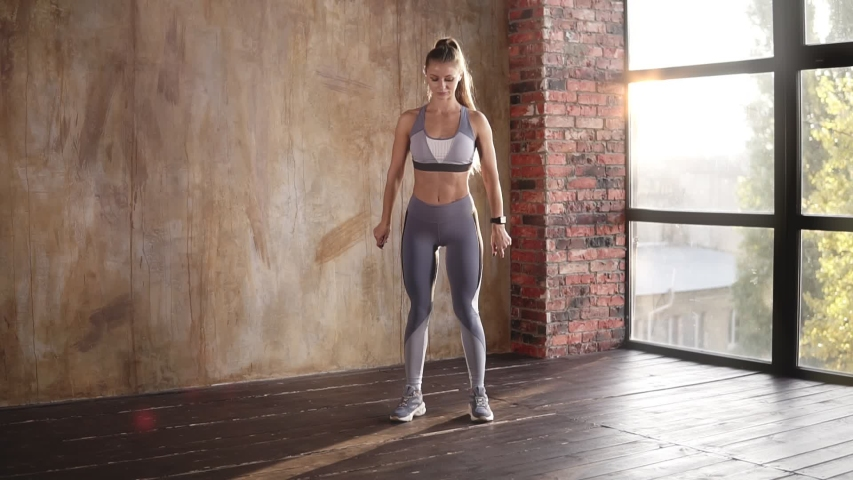 Full-length shot of the sportive attractive blonde girl doing the wrist-circling exercise to warm up in the modern empty studio. Fitness for beginners. Slow motion #1041475933