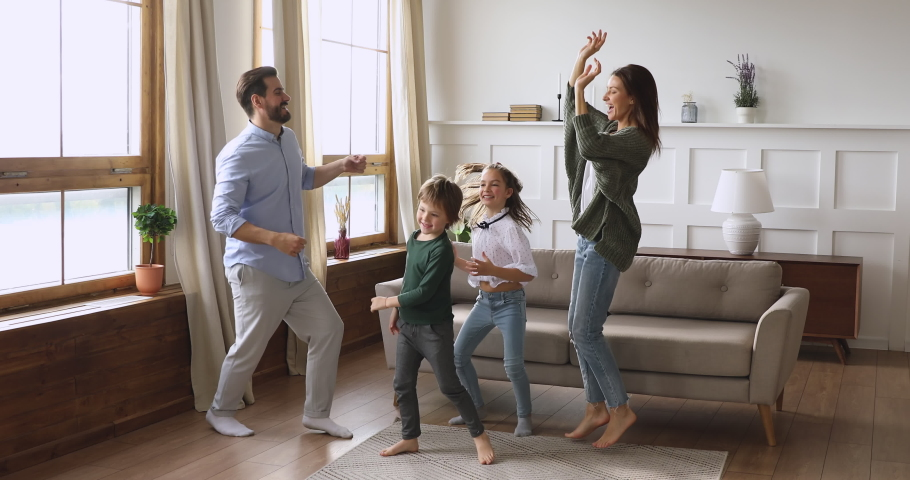 Crazy happy family young adult parents mum dad and cute funny active little children kids listening music dancing jumping together having fun in modern living room enjoying leisure lifestyle at home | Shutterstock HD Video #1041538723