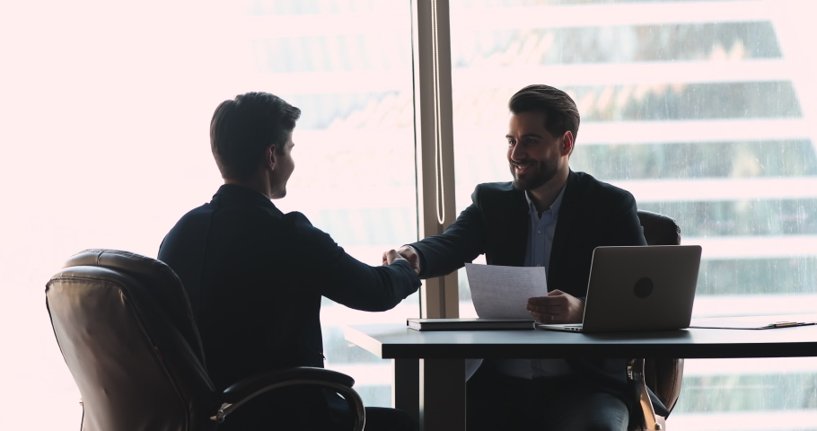Confident businessman company employer wear suit handshake hire male vacancy candidate employee offering professional contract at job interview sit at modern office table, hr staff employment concept | Shutterstock HD Video #1041547633