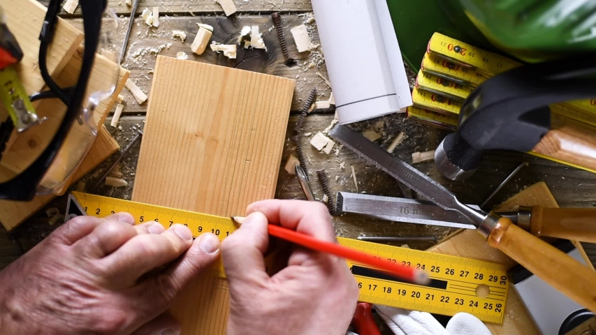 View from above. Carpenter with the pencil and the carpenter's square drawing the cutting line on a wooden board. Construction industry, do it yourself. Wooden work table. | Shutterstock HD Video #1041578353