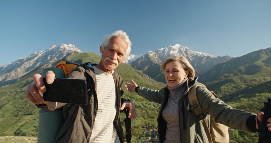 Mature caucasian couple travelling together, having a nordic walking hike in spring mountains, then stopping to take a picture on smartphone, spending time after retirement - recreational pursuit #1041601303