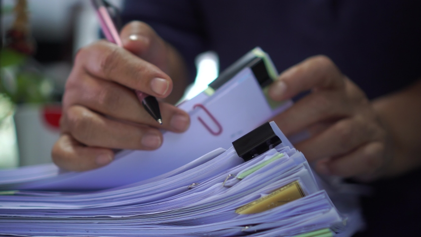 Auditor or businessman checking searching document legal for prepare paperwork or report for analysis information, accountant in workload data contract partner deal in workplace at office, 4k | Shutterstock HD Video #1041668263