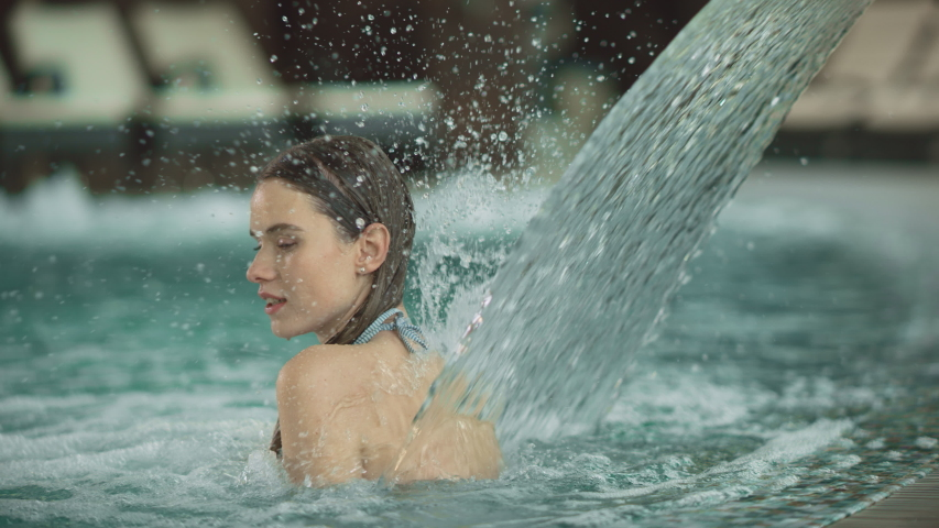 Closeup young woman getting hydrotherapy in pool at spa hotel. Beautiful girl having spa treatment at wellness center. Pretty girl relaxing with hydro massage at luxury pool. | Shutterstock HD Video #1041957283