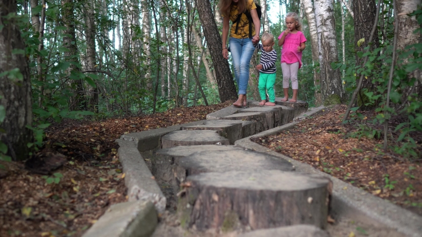 Mother with little son and daughter walking on healthy barefoot path. Sensory path with different surfaces. Camera movement follow shot with gimbal. | Shutterstock HD Video #1042046443