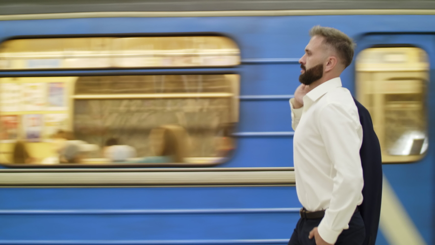 Side view on businessman in white shirt walking on subway station near moving train | Shutterstock HD Video #1042093483