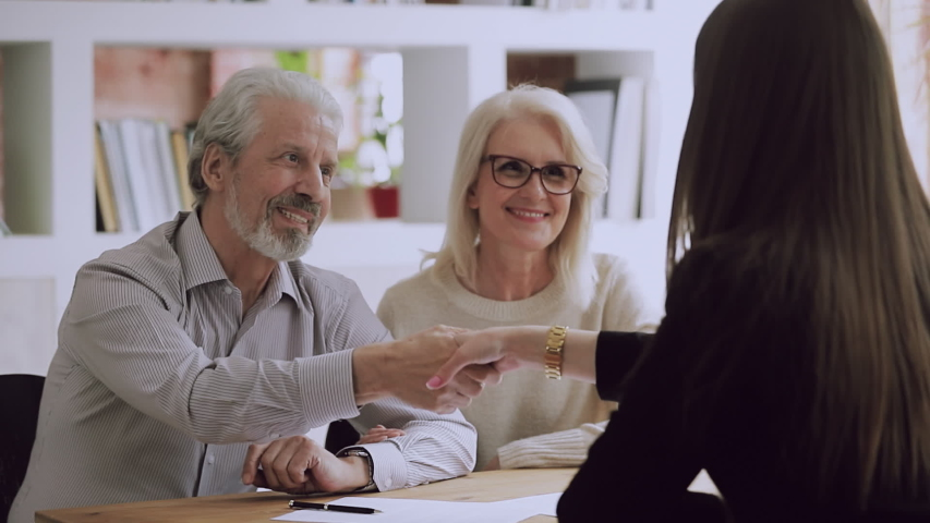 Happy middle aged family couple meeting female real estate agent, financial advisor or lawyer, discussing contract details, making agreement at office. Satisfied client shaking hands with saleswoman. | Shutterstock HD Video #1042151323