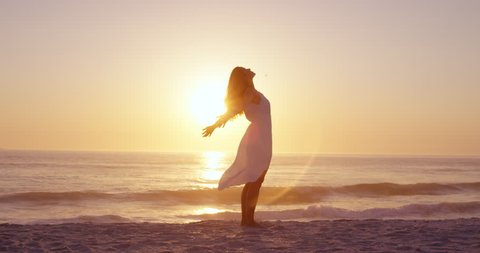 Free happy woman arms outstretched enjoying nature on beach at sunset face raised towards sky slow motion RED DRAGON