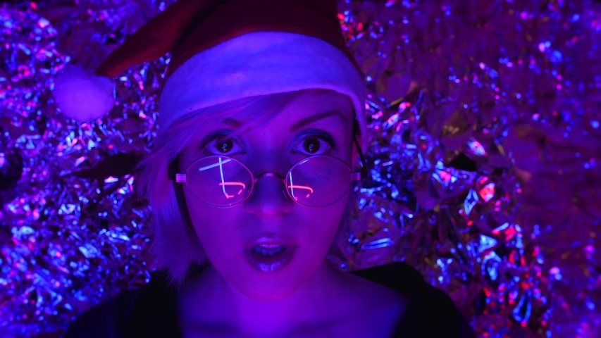 Cute girl in Santa costume celebrates and gifts a box. Red hat and round glasses. Neon blue and pink light at night in studio with space design | Shutterstock HD Video #1042239823