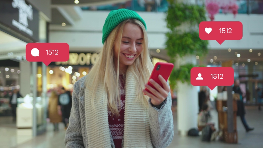 NEW YORK - April 5, 2019: Portrait smiling young woman use phone in shop mall typing social media icons with like comment follower counter quick increase blogger influencer adult communication slow | Shutterstock HD Video #1042244983