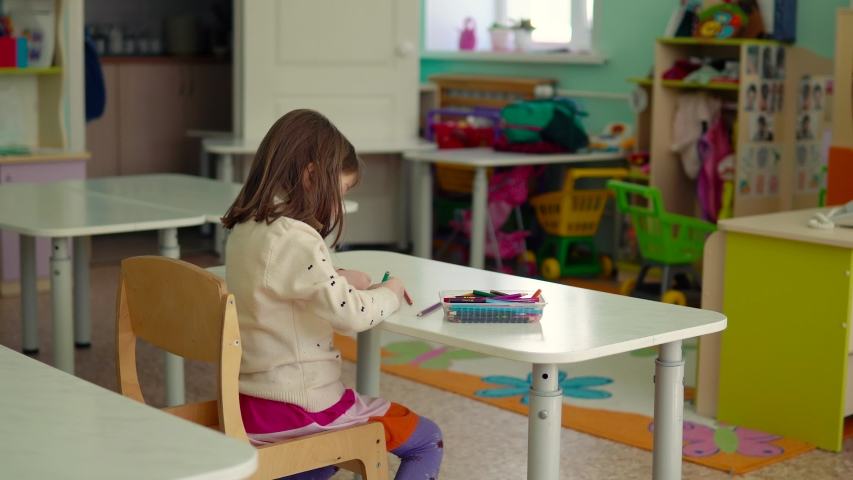 Child, girl 5-6 years old, draws, sitting at the table. School, kindergarten, education concept. School, kindergarten, education concept.   Shutterstock HD Video #1042317403
