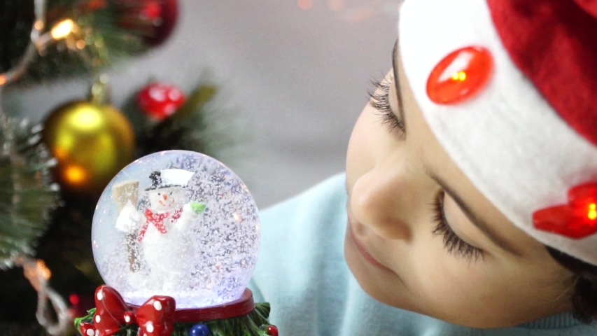 Little boy shook the snow globe, put it on the floor and peep inside it as the snow falls on the santa claus located inside this snow globe. 4K | Shutterstock HD Video #1042367293