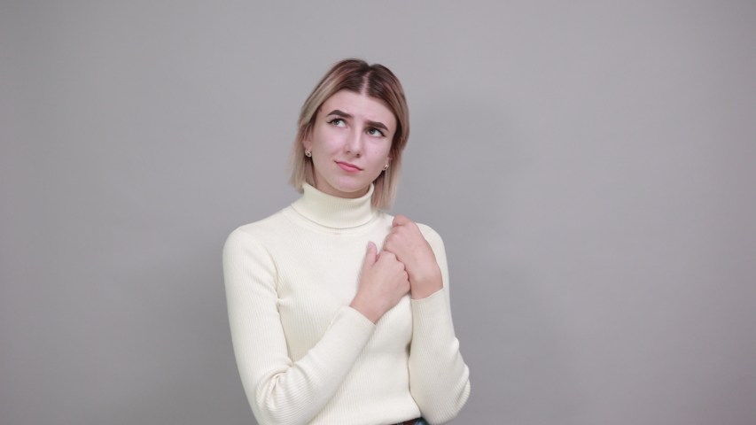 Young pretty attractive woman looking up, opened eyes with the hand on the chest on isolated white background wearing fashion clothes | Shutterstock HD Video #1042410013
