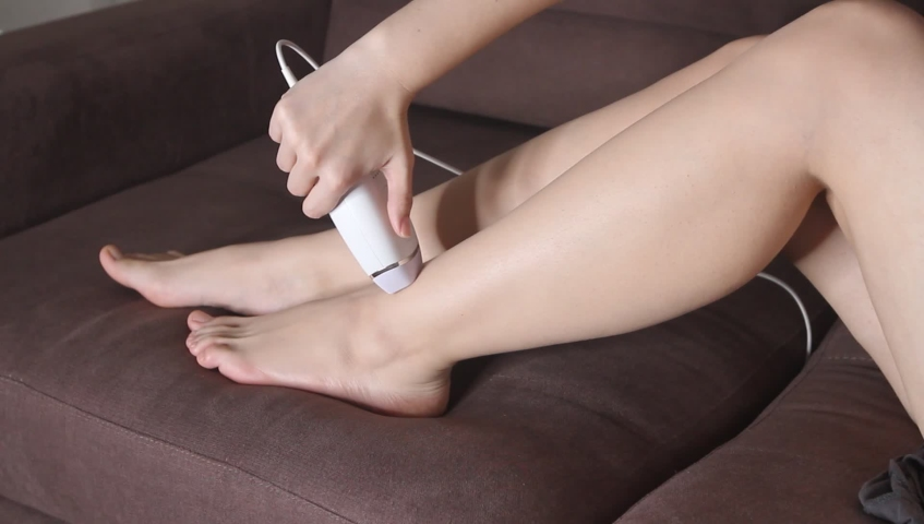 Woman using photoepilator for hair removal at home. Epilator for legs photoepilation. Removing hair on legs | Shutterstock HD Video #1042499143