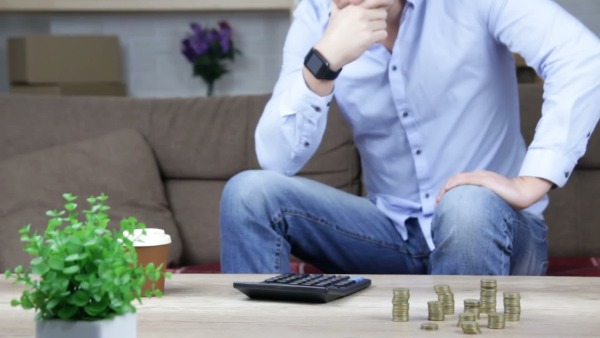Worried man counting money on table, price inflation, low-paid job, savings   Shutterstock HD Video #1042534363