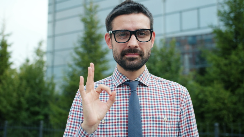 Confident entrepreneur attractive bearded man is showing OK hand gesture smiling standing outdoors near office center looking at camera. People and job concept.   Shutterstock HD Video #1042538683