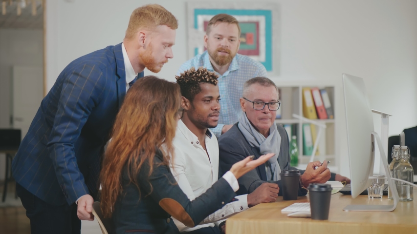 Full concentration at work. Group of diverse businesspeople working on computer and communicating while sitting at the office desk together | Shutterstock HD Video #1042547623
