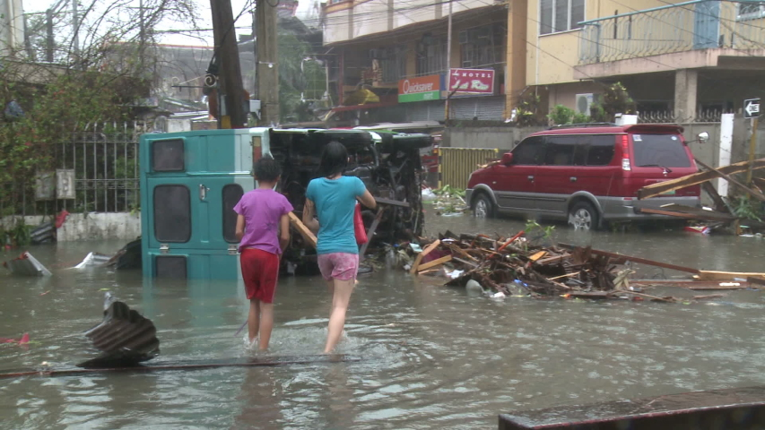 LEYTE, PHILIPPINES - NOVEMBER 2013: People Walk Through Flooded Street After Major Hurricane Storm Surge Hits City