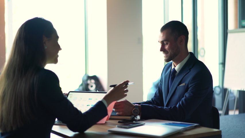 Business persons in formal wear communicating about market strategy discussing data information indoors, Caucasian colleagues have productive brainstorming during teamwork  | Shutterstock HD Video #1042560043