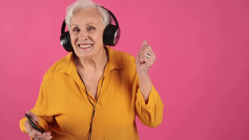 Close up portrait of a very old grandma cool incendiary dancing jiga to the music in big headphones from the phone. isolated, pink background,