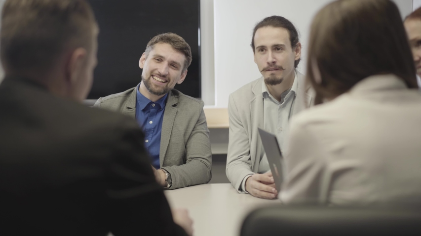 Shooting over shoulder of male Caucasian office workers in suits listening to their colleagues or business partners. Team discussing new project on meeting. Teamwork, communication, deal. | Shutterstock HD Video #1042585033