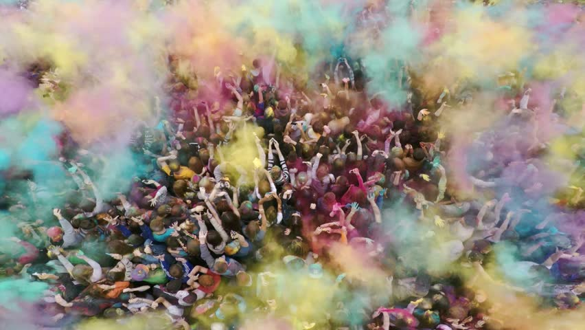 Russia, Chelyabinsk, 13 June 2015: Aerial flight above dancing crowd on Holi Festival Of Colors. Crowd of people colored powder and having fun.  - 4K stock video clip