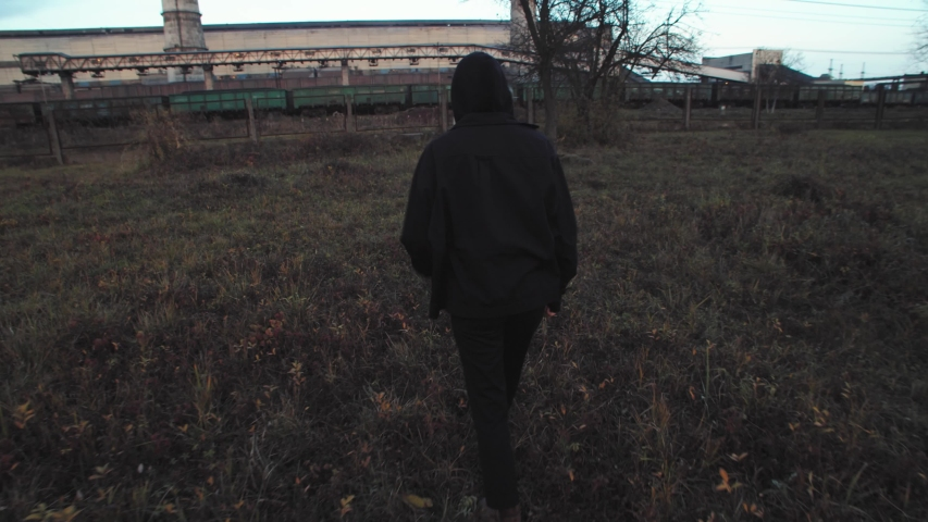 Rear view of young female activist in black suit and face mask standing in front of working industrial factory. Private power plant station. Polluted environment. Developing eco frienldy system. | Shutterstock HD Video #1042593463