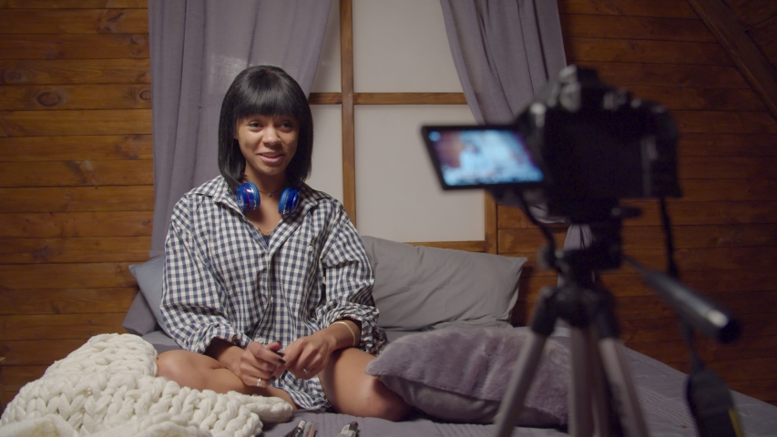 Stylish confident pretty african american female vlogger in domestic clothing with makeup cosmetics recording video for blog at home, communicating and sharing beauty advice on camera for her vlog. | Shutterstock HD Video #1042604683