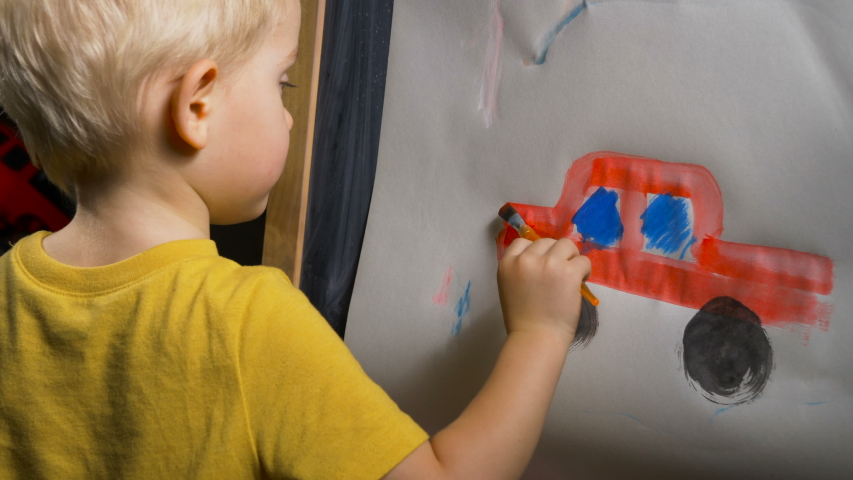 Little boy (preschooler) is painting a red toy truck with acrylic paint. Indoor kids activities, daycare, classroom. Early education concept, child creativity and art | Shutterstock HD Video #1042655653