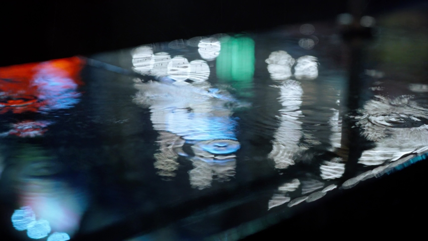 Closeup Rain drops Falling On puddle with lights reflection on city sidewalk. Rain Drop With Street Lights and colorful traffic lights At Night Blur Bokeh Abstract 4k stock footage | Shutterstock HD Video #1042698823