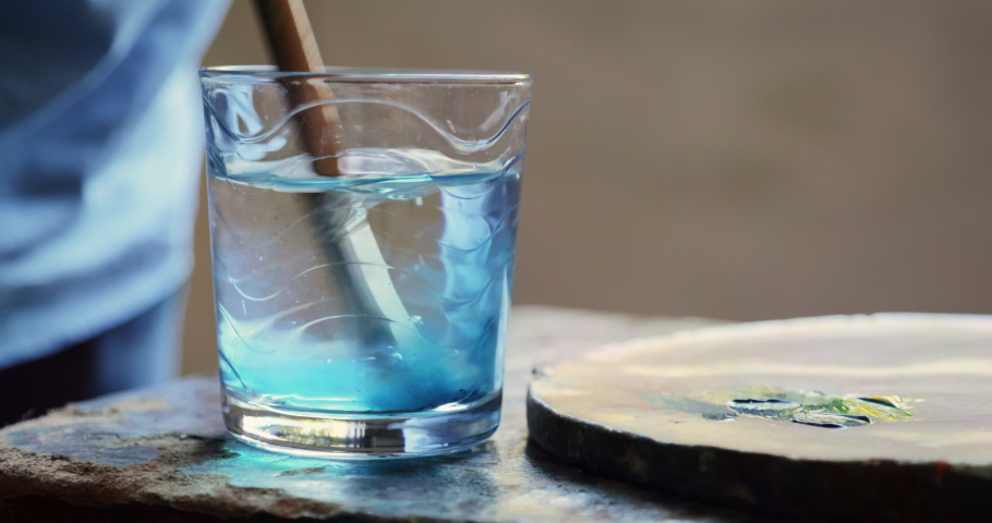 Elderly people painting for hobby. Active senior person at school of arts. Leisure activity, lifestyle, recreation, passion, fun. Closeup of old brush being cleaned in glass of water. Slow motion | Shutterstock HD Video #1042704433