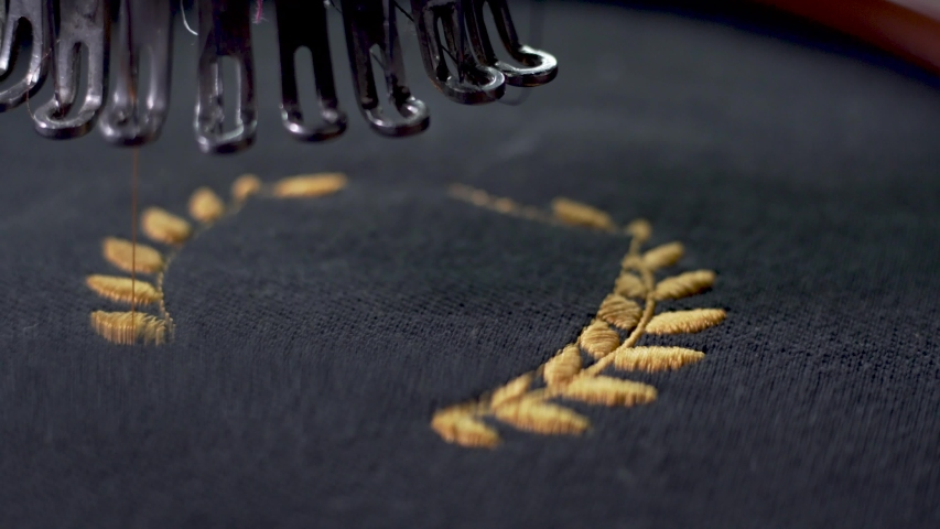 Close up of Sewing needle completing a whole wreath with golden twine, on black fabric | Shutterstock HD Video #1042754653