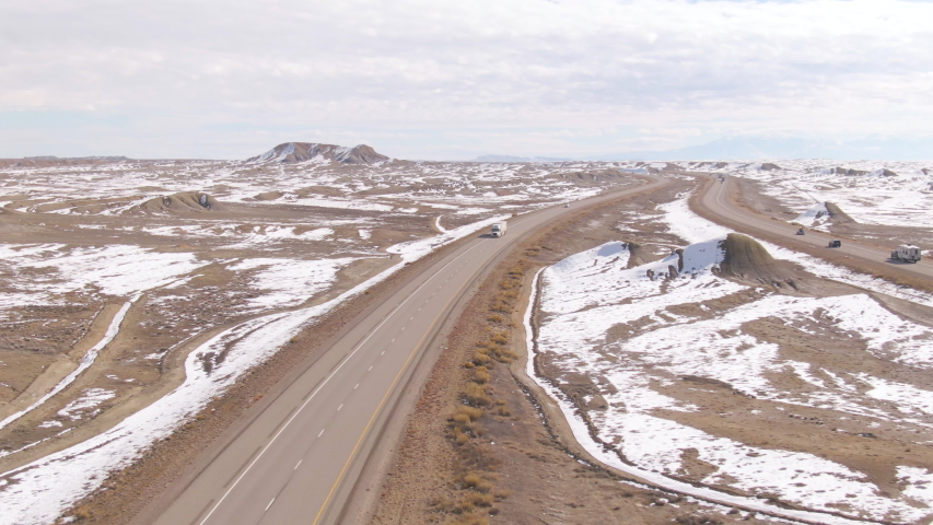 DRONE: Flying above a highway as white truck crosses the snowy desert in Utah. 18 wheeler speeds along the interstate highway crossing the rugged wintry wilderness. Cars and truck cross a desert. | Shutterstock HD Video #1042795723