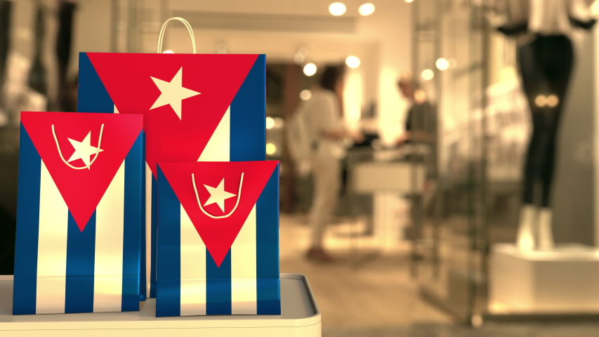 Flag of Cuba on the paper shopping bags against blurred store entrance. Retail related clip | Shutterstock HD Video #1042800763