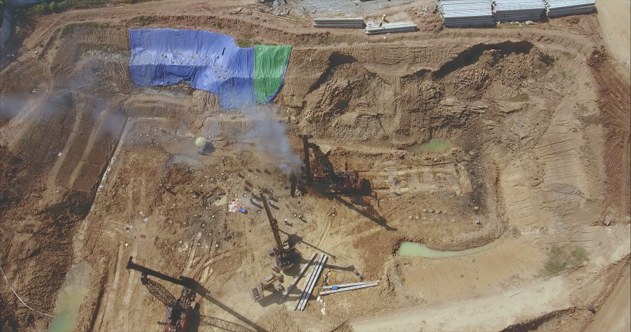 Drone shot looking down at the construction site.  Drilling piles with heavy machinery in use  | Shutterstock HD Video #1042809853