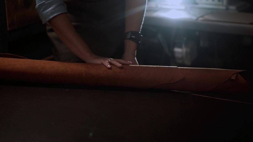 Close up craftswoman working with leather belt. Shoe production process in factory. Close up leather craftsman working with natural leather using hammer. Handmade concept, Working process with leather | Shutterstock HD Video #1042827613